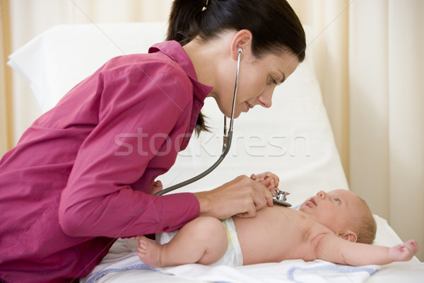 Stock photo: Doctor giving checkup with stethoscope to baby in exam room