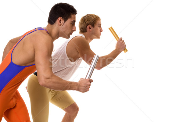 Stock photo: Track and field athletes competing in a relay race. Studio shot over white.