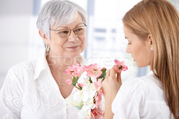 Stock photo: Mature mother and young daughter with blossom