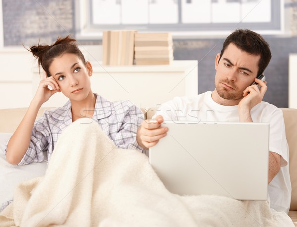 Stock photo: Young couple in bed man working woman bored