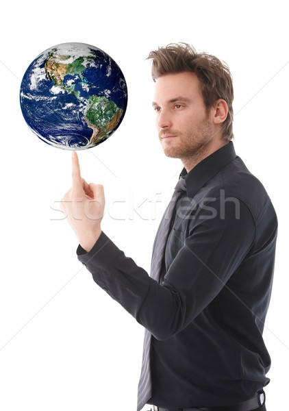 Stock photo: Goodlooking man balancing a globe on forefinger