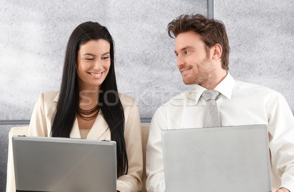 Stock photo: Elegant couple sitting on sofa using laptop