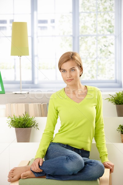 Stock photo: Attractive woman sitting at home in vivid green
