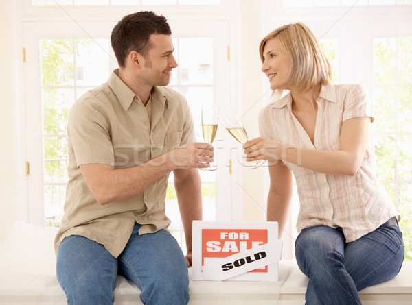Stock photo : Young couple celebrating new home, clinking champagne ...