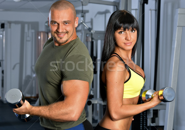 Stock photo: Man and woman are doing exercises in a sport club.