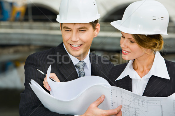 Confident female worker is showing a architectural plan to her chief