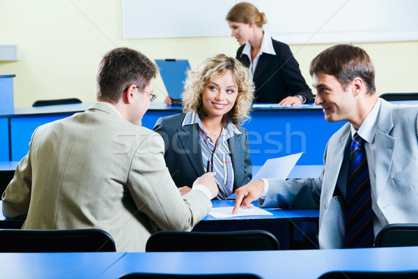 Group of people sitting at the blue table and discussing business questions in the conference room