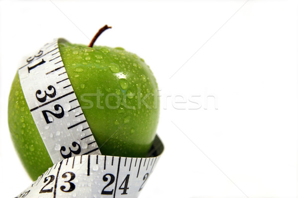 Stock photo: Measurement tape wrapped around green apple