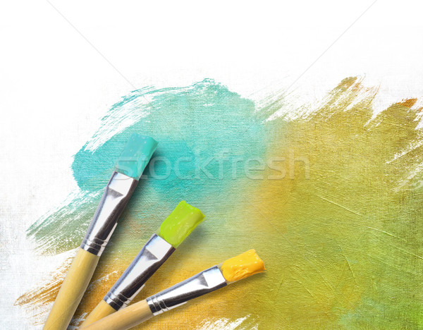 Stock photo: Artist brushes with a half finished painted canvas
