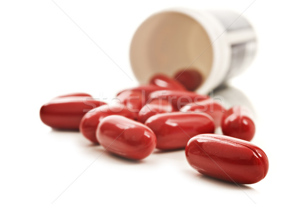 Stock photo: Red pills an pill bottle on white background