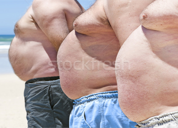 Stock photo: Close up of three obese fat men of the beach
