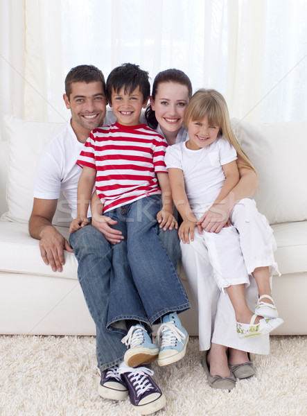 Family in living-room sitting on sofa together