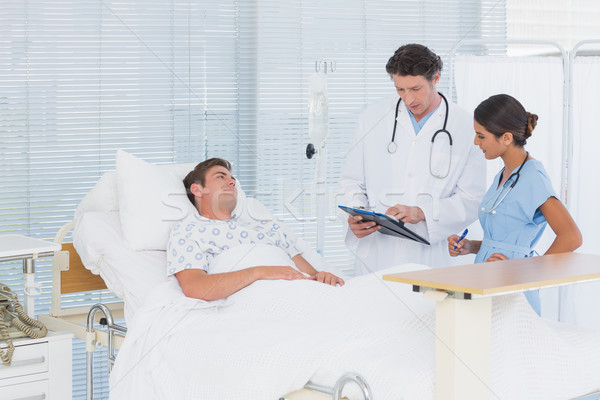 Doctors taking care of patient in hospital room