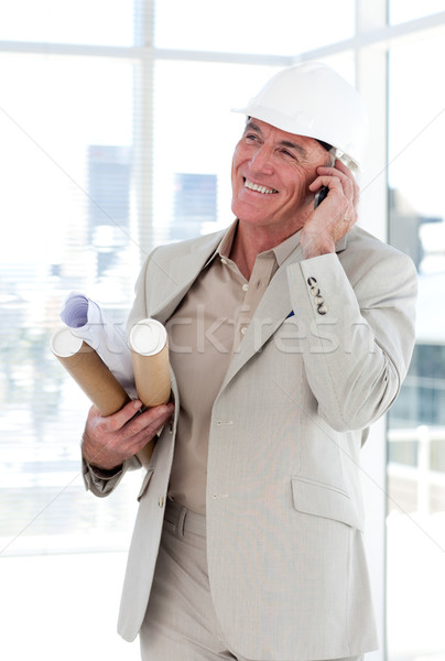 Stock photo: Senior architect on phone carrying blueprints