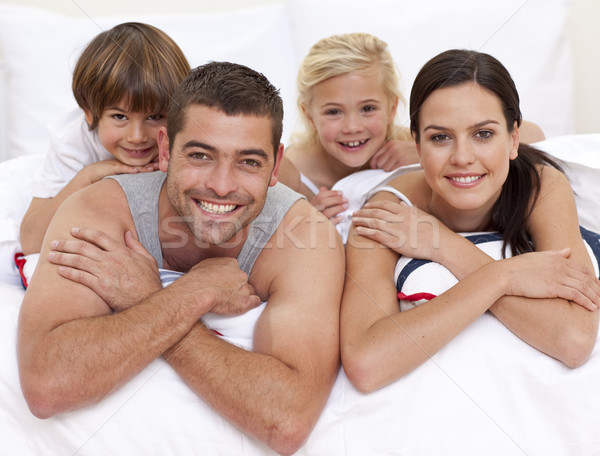 Happy young family playing in parent\'s bed