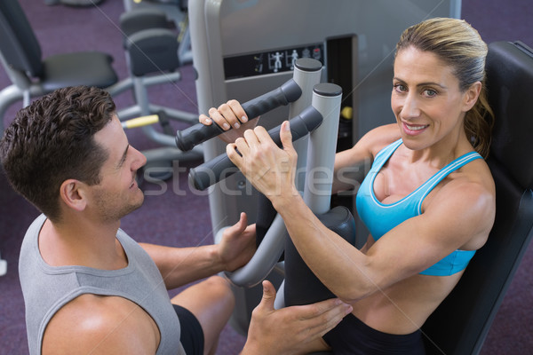 Personal trainer coaching smiling female bodybuilder using weight machine at the gym