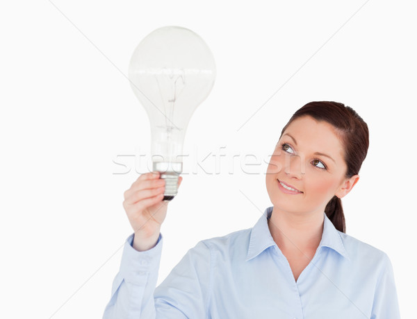 Gorgeous red-haired woman holding a light bulb while standing on a white background