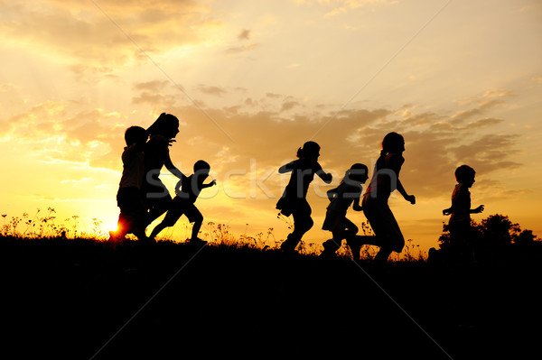 Silhouette, group of happy children playing on meadow ...